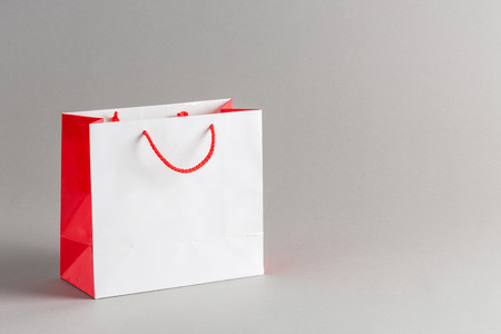 shopping bags: White and red color paper shopping bag isolated on gray background Stock Photo