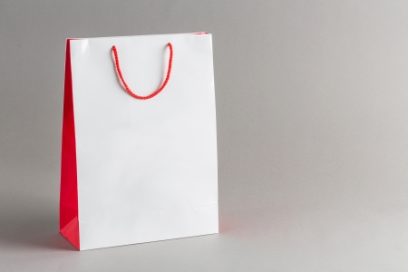 shopping icon: White and red color paper shopping bag isolated on gray background Stock Photo