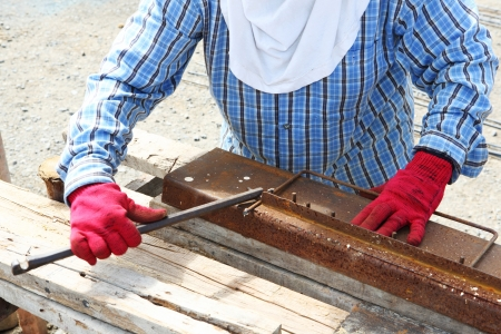 jig: Rebar bending by worker on rusty jig in construction site Stock Photo