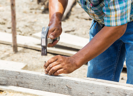 Worker hammering nail into wood at construction site photo