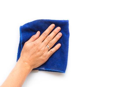 mujer limpiando: Cierre de la mano con el azul limpieza pa�o en la pared blanca Foto de archivo