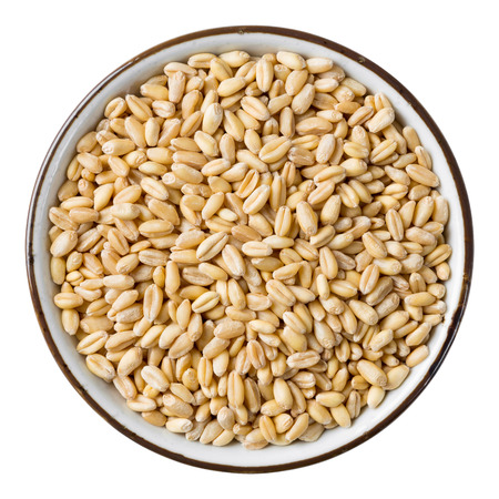 Close up wheat grain in ceramic dish isolated on white - with path photo