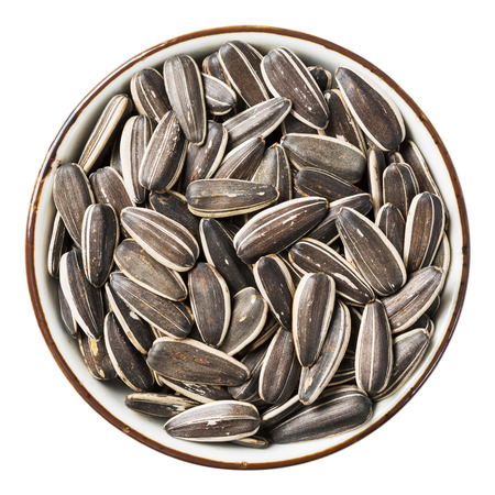 sunflower seeds: Close up sunflower seed in ceramic dish isolated on white - with path
