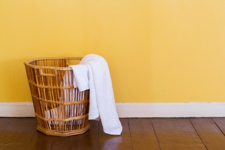 laundry room: Close up white color used towels in wicker basket Stock Photo
