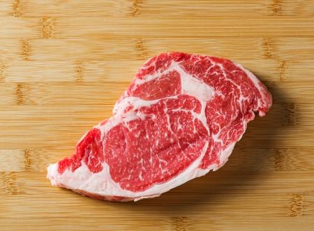Raw aged beef ribeye steak on bamboo chopping board