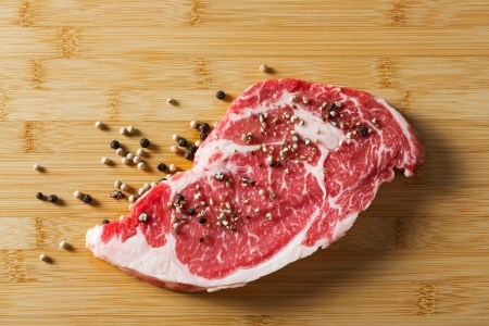 Aged beef ribeye steak with black and white pepper on bamboo chopping board
