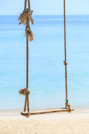 Close up old and weathered rope and wooden swing by the beach and blue sea photo