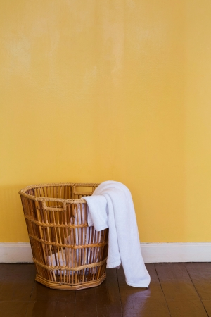 dirty room: Close up white color used towels in wicker basket Stock Photo