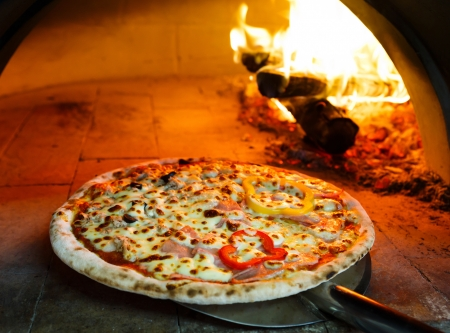 oven: Close up pizza in firewood oven with flame behind