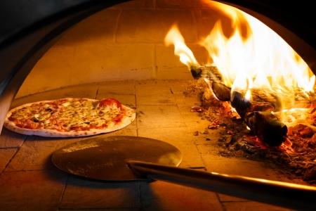 뒤에 불꽃 장작 오븐에서 피자를 닫습니다