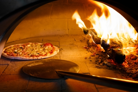 Close up pizza in firewood oven with flame behind