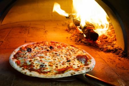 Close up de pizza en horno de leña con llama detrás