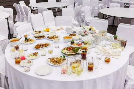 Waste food on round table after dinner in party room photo