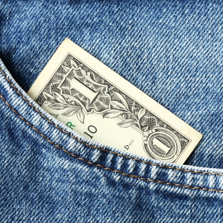 Close up one US dollar banknote in blue jeans pocket photo