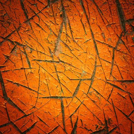 Close up vignette style orange color cracked paint texture photo