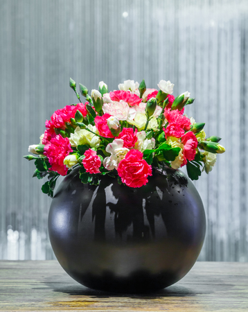 flower arrangements: Close up white yellow and red color Carnation flower in black ceramic pot