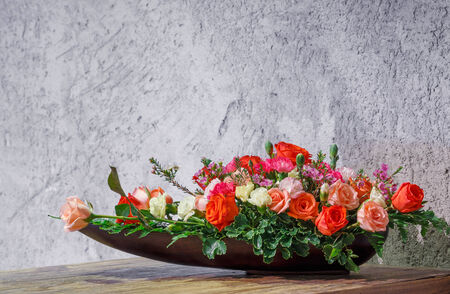 Close up rose and carnation flower arrangement in wooden tray on table beside grunge concrete wall photo