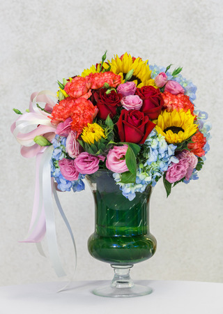 Close up flower bouquet in in glass vase on white table beside grunge concrete wall photo