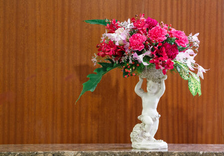 Close up flower bouquet in roman cupid ceramic vase on stone table beside wooden wall photo