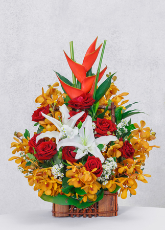 Close up rose orchid lily and bird of paradise flower bouquet in wooden basket on table beside grunge concrete wall photo