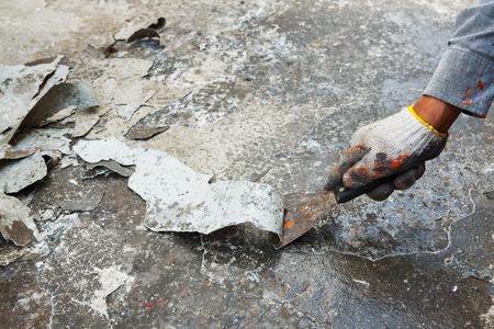 コンクリートの床に古いペンキを削り労働者の手を閉じる