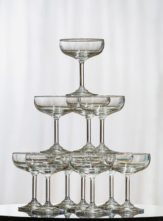 Stack of champagne glasses on glass table in wedding party photo