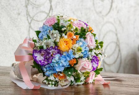 Close up rose carnation hydrangea gypsophila flower bouquet on wooden table  photo
