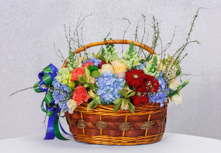 Close up gerbera hydrangea carnation rose orchid flower in wood basket on table beside grunge concrete wall photo
