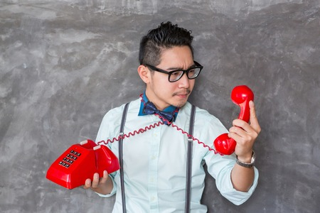 Young man looking the red telephone with bad felling face photo