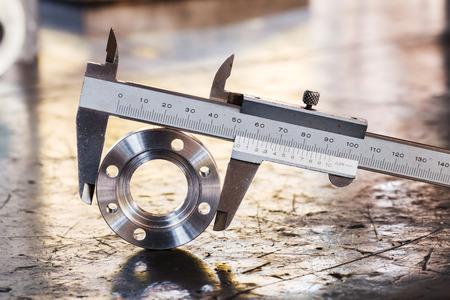 flange: Close up vernier caliper measure diameter of stainless steel flange