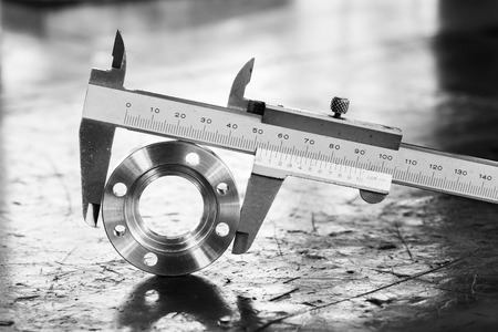 Close up vernier caliper measure diameter of stainless steel flange