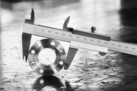 quality work: Close up vernier caliper measure diameter of stainless steel flange