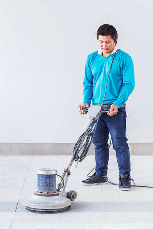 Asian worker using floor polishing machine in office building photo