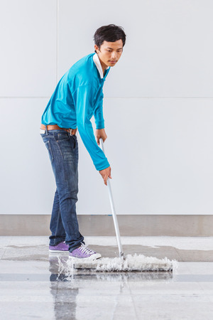 squeegee: Asian worker using wiper or squeegee to clean floor surface