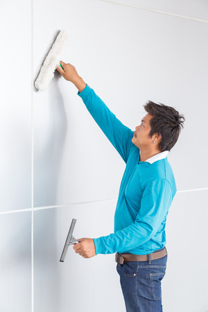 Asian worker use glass washer and wiper or squeegee to cleaning wall in office building  photo