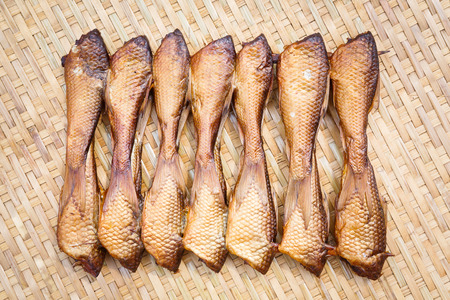 common market: Close up Crispy smoke dried siamese mud carp fish on bamboo threshing basket Stock Photo