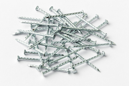 close fitting: Close up galvanized iron nails for furniture fitting on gray color paper - deep focus image - stacked photo Stock Photo