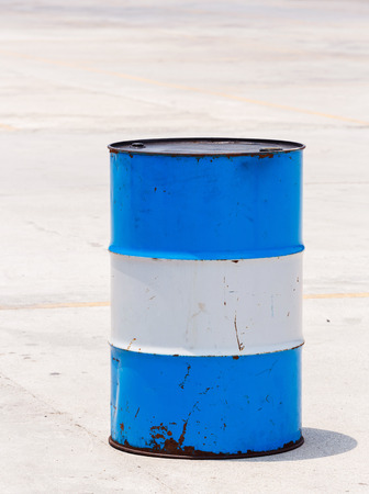 standard steel: Old and dirty oil barrel tank isolated on concrete floor in bright sunlight Stock Photo