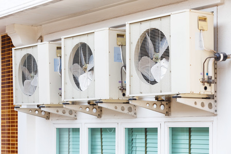 Close up air conditioners installation outside of building near glass windows