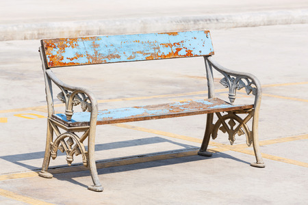 Old and weathered wooden bench with cast aluminium legs on concrete floor in strong sunlight photo
