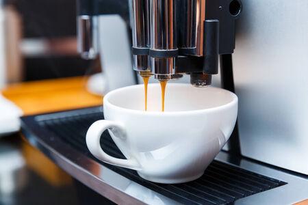 Close up espresso preparing in white ceramic cup from automatic coffee maker machine photo