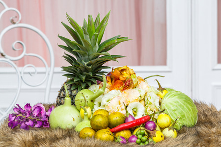 Close up Thai vegetables and fruits decoration with flowers on brown color fur beside windows photo