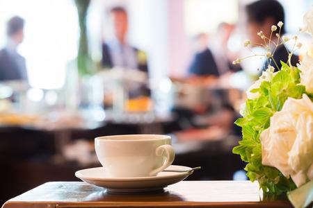 bouquet fleur: Gros plan sale tasse de caf� avec une cuill�re et plat � c�t� de bouquet de fleurs dans une salle de r�union � l'heure de la pause caf� avec les gens floues fond - chaude photo de ton Banque d'images