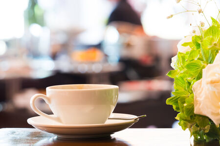 Close up dirty coffee cup with spoon and dish beside flower bouquet in meeting room on coffee break time with blurry people background - warm tone photo photo
