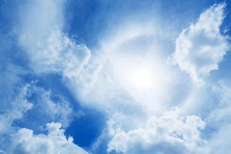 Sun halo or corona phenomenon in cloudy and blue the sky photo