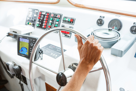 Close up captain hand on boat steering wheel photo