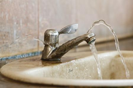 llave de agua: Close up de fugas y la válvula de la ruina en el baño antiguo Foto de archivo