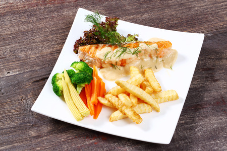 Close up white sauce salmon steak with dill and vegetable photo