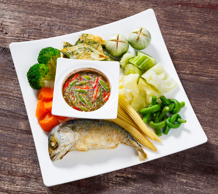 Close up spicy shrimp paste dip sauce served with deep fried mackerel and vegetable photo