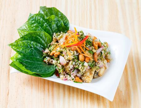 betel leaf: Close up Deep fried barramundi with Thai style spicy salad wild betel leaf Stock Photo